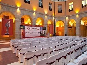 montaje de sillas plegables con funda blanca y lazos burdeos en diseño damero en sede Comunidad de Madrid para entrega de premios