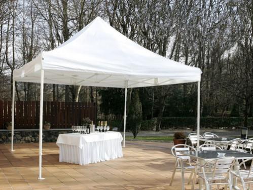 Alquiler mesa rectangular con faldón y mantel blancos montada bajo carpa blanca para cátering