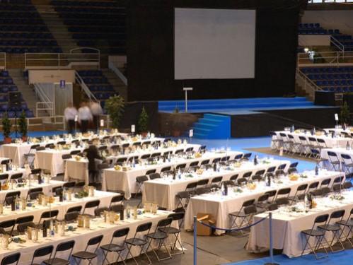 Alquiler montaje de convención con mesas con mantel y sillas plegables a dos caras en hileras con escenario y gran pantalla