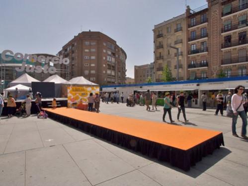 Instalación de Escenarios en exteriores enmoquetados en naranja con faldón negro y escaleras de acceso a pasarela de moda enmoquetada igualmente